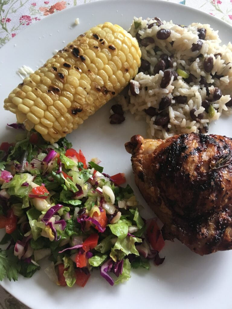 jerk chicken, black beans and rice, chopped salad, corn on the cob